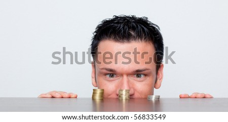 Businessman looking on coins tower on table as concept for money growth