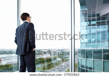 Businessman looking out of his office on the opposite building