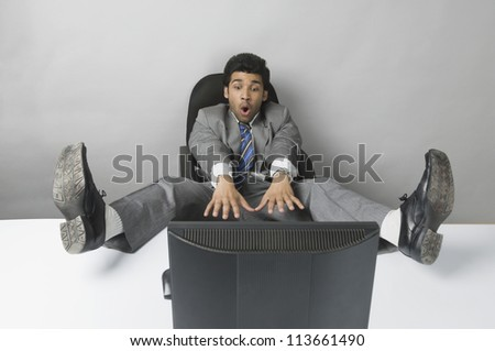 Businessman looking surprised with his feet up in front of a desktop PC - stock photo
