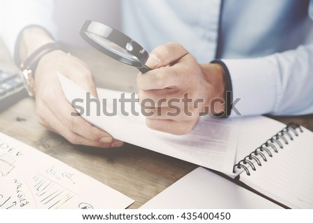 Businessman looking through a magnifying glass to documents #435400450
