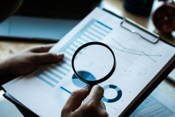 Businessman looking through a magnifying glass to documents. Business assessment and audit. Magnifying glass on a financial report.Concept of search.