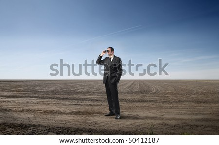 Businessman looking through a pair of binoculars on a field - stock photo