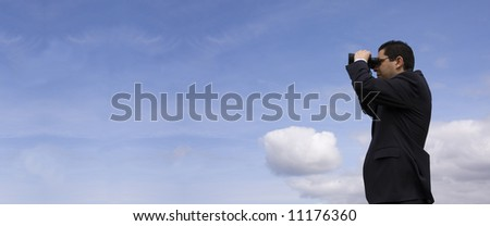 Businessman looking through binoculars with a blue sky as background (panoramic photo)