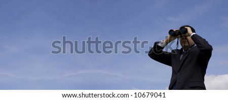 Businessman looking through binoculars with a blue sky as background (very wide photo) - stock photo