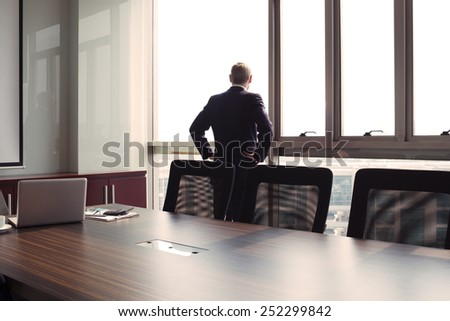 Businessman looking through the office window, rear view