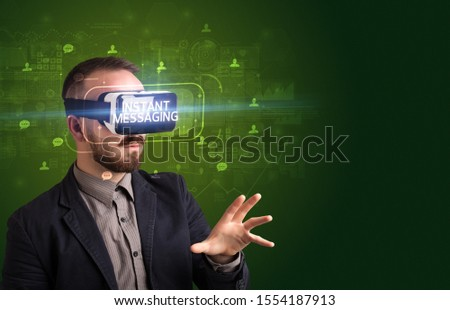 Businessman looking through Virtual Reality glasses with INSTANT MESSAGING inscription, social networking concept