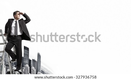 Businessman looking to horizon over urban background.