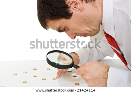 Businessman looking to the coins through a magnifying glass