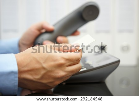 businessman looks on business card for information to make a call