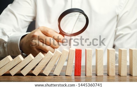 Businessman looks on collapse domino effect. Stress resistance business. Financial stability. Recovery business. Evaluation of cash risks. Creating a strategy. Management and planning. Decision making
