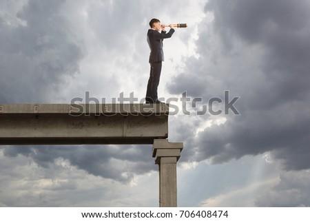 Businessman looks through a telescope. Concept for business #706408474
