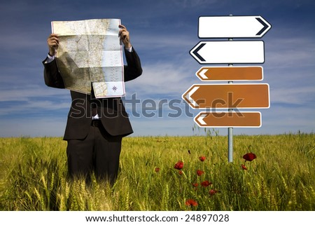 businessman lost in field using a map - sign direction - stock photo