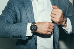 Businessman luxury style. Men style.correct button on jacket, hands close-up, dressing, man's style, stylish man.Fashion portrait of young businessman handsome model man in casual cloth suit.