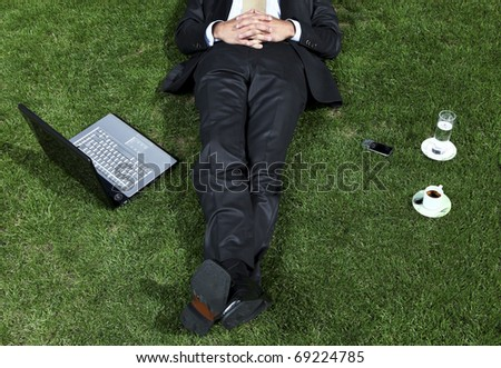 businessman lying in a park with his laptop