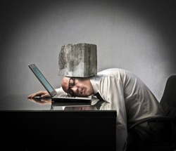 Businessman lying on a laptop with a rock squeezing his head against the laptop keyboard
