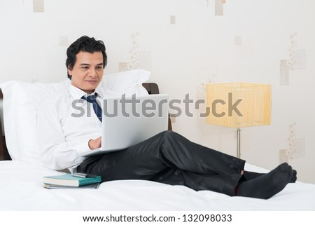 Businessman lying on the bed with a laptop