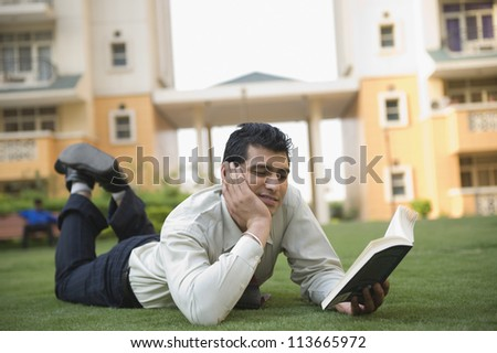 Businessman lying on the grass and reading a book