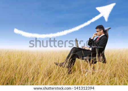 Businessman make a call while sitting outdoor under up arrow sign