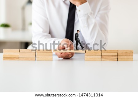 Businessman making a bridge between two stacks of wooden pegs for the other businessman to walk across.