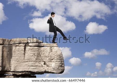 Businessman making a danger and step falling from a rock - stock photo
