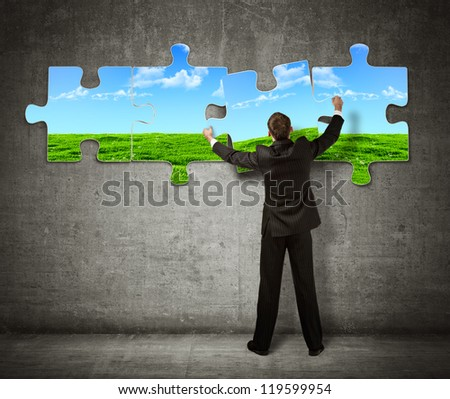 Businessman making a puzzle on the wall with  picture of nature