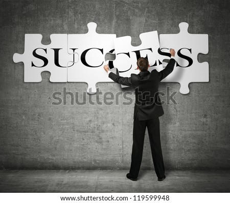 Businessman Making A Puzzle On The Wall With The Word Success