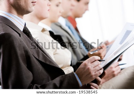 Businessman making notes during convention with row of people at background