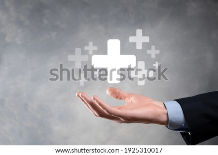 Businessman, man hold in hand offer positive thing such as profit, benefits, development, CSR represented by plus sign.The hand shows the plus sign. Foto stock ©