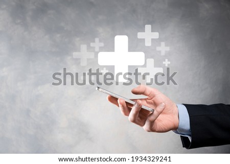 Businessman, man hold in hand offer positive thing such as profit, benefits, development, CSR represented by plus sign.The hand shows the plus sign. Photo stock ©