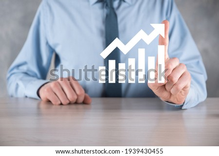 Businessman man holding a graph with positive profits growth. plan graph growth and increase of chart positive indicators in his business.more profitable and growing Foto stock ©