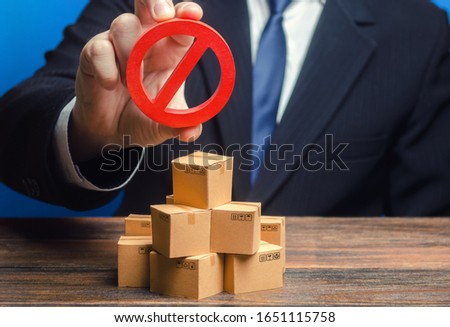 Businessman man official holding red prohibition sign NO over boxes with goods. Out of stock. Embargo trade wars. Restriction import, ban export of dual use goods to countries under sanctions. Foto d'archivio ©