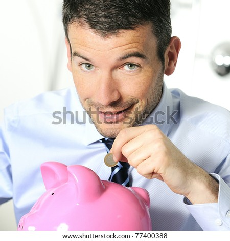 businessman matting a coin in the piggy-shaped pink pig