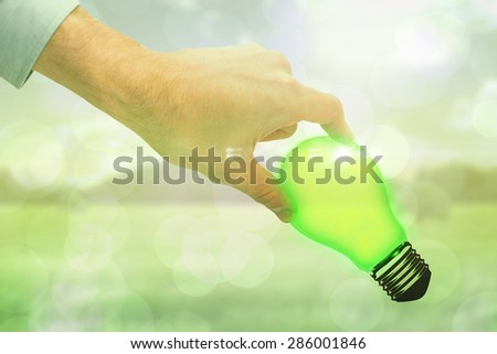 Businessman measuring something with these fingers against green abstract light spot design