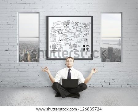 businessman meditating in brick loft