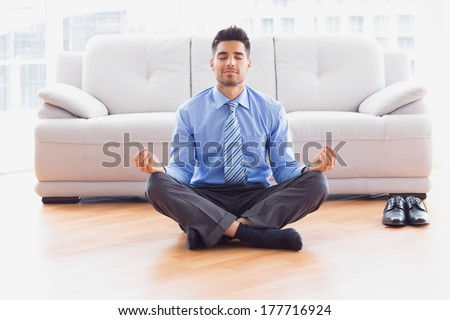 Businessman meditating in lotus pose on the floor in the office