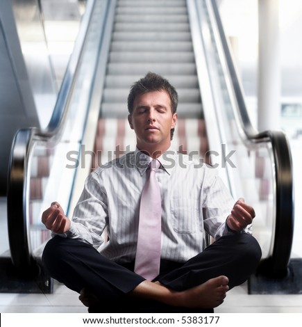 Businessman meditating in lotus position in front of an escalator indoor.