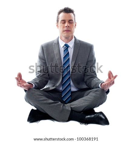 Businessman meditating in lotus position isolated over white background