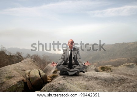 Businessman meditating on a rock in the mountains