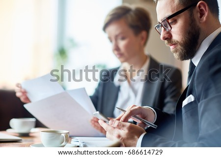 Businessman messaging in smartphone while his colleague looking through papers