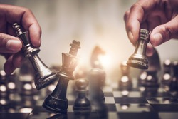 Businessman moving chess piece on chess board game concept for ideas and competition and strategy, business success concept, business competition planing teamwork strategic concept.