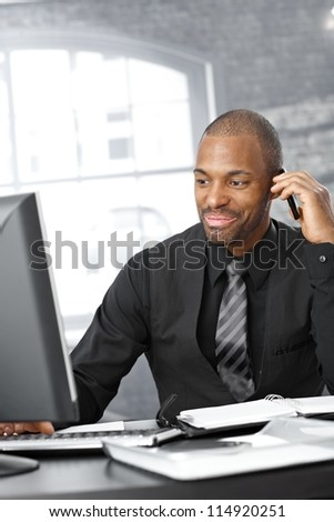 Businessman multitasking, working with computer and having mobile phone call, smiling.