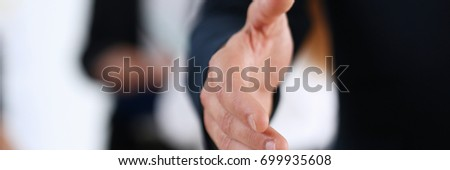 Businessman offer hand to shake as hello in office closeup. Serious business, friendly support service, excellent prospect, introduction or thanks gesture, gratitude, invite to participate concept #699935608