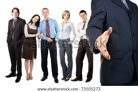 Businessman offering for handshake with colleagues standing in the background