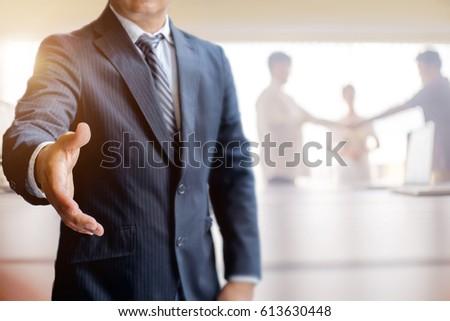 Businessman Offering Handshake in meeting room. Success Concept.