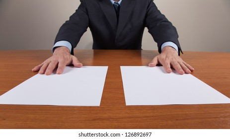 Stock photo of a businessman in the office with two white sheets. The sheets are put on the table and expresses two proposals or choice.