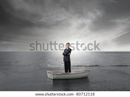 Businessman on a boat in the middle of the sea