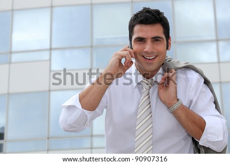 Businessman on a mobile phone outside a city building - stock photo
