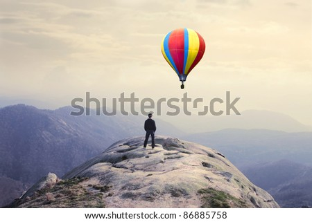 Businessman on a peak observing a hot-air balloon