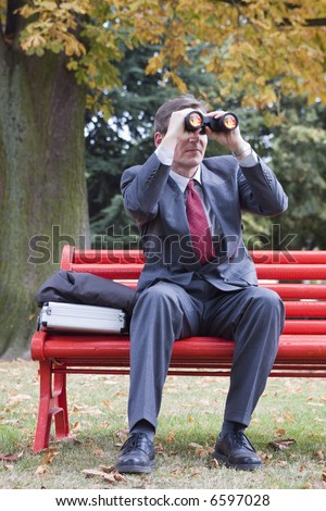 Businessman on a red park bench looking through binoculars