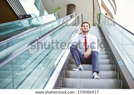 businessman on an escalator stairs talking on mobile phone #159086417